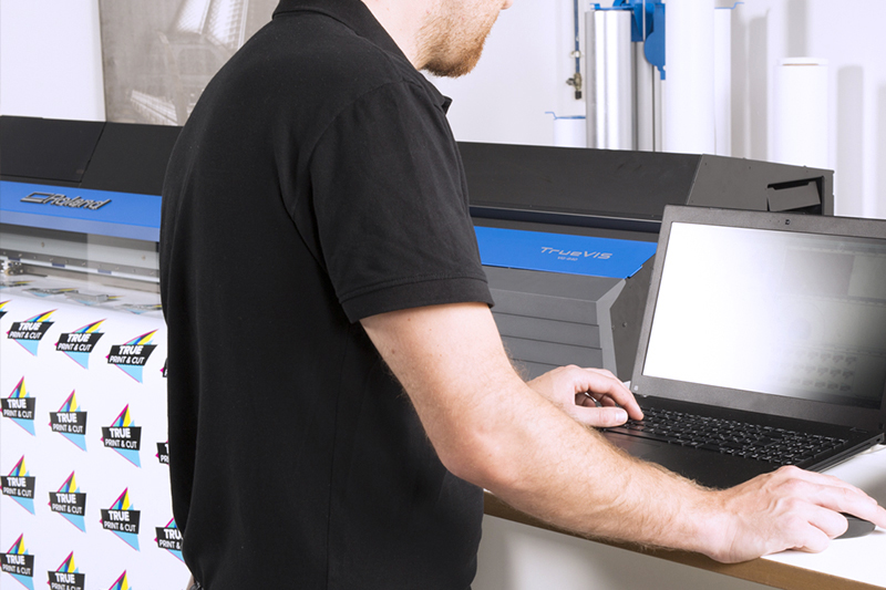 VersaWorks 6 shown on laptop next to TrueVIS VG printer/cutter